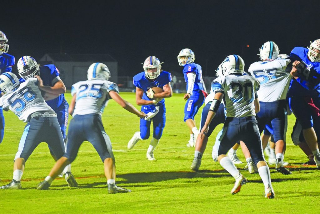 Luke Ehret (13) rushes for a one-yard touchdown during the Hornets' 47-7 victory over the Pinckneyville Panthers for the Homecoming Game while Cole Malawy looks on. The Hornets remain undefeated this season, 7-0.