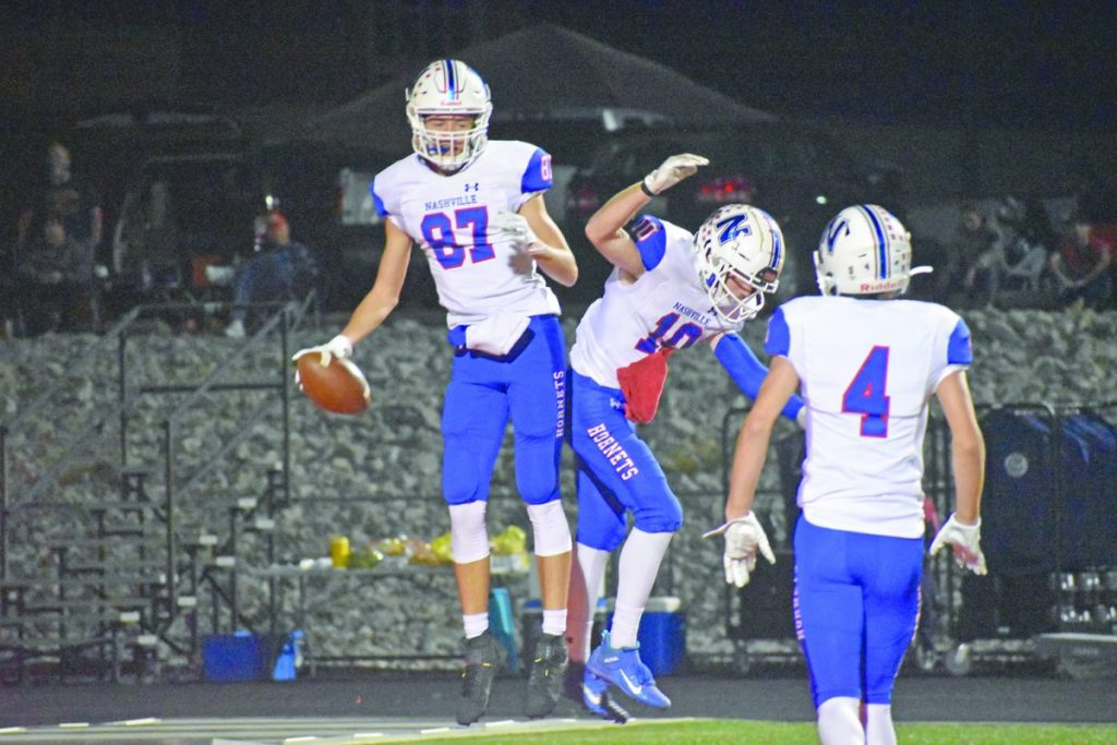 Jaxon Goforth (87) celebrates in the air with Nick Miller (10) after scoring a touchdown in the first quarter Friday night. The Hornets kept off a Lions rally to win 41-38.