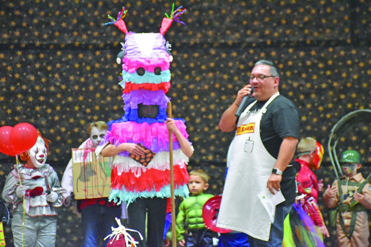 Lily Emge, left, wins the top overall costume for her pinata