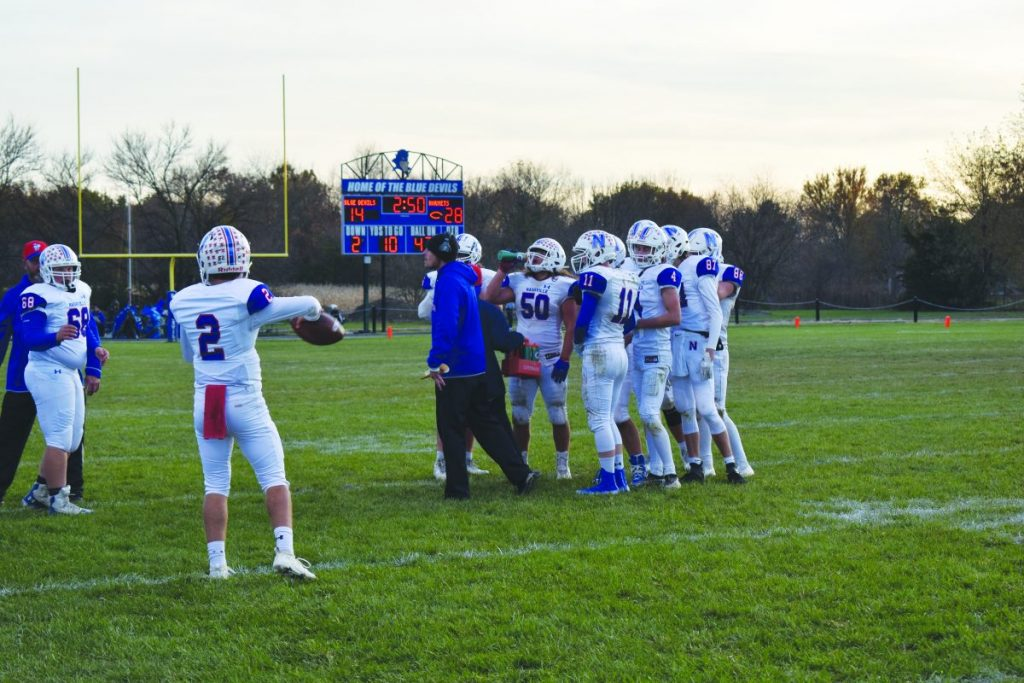 Coach Kozuszek and his team discuss strategy late in the game Saturday.