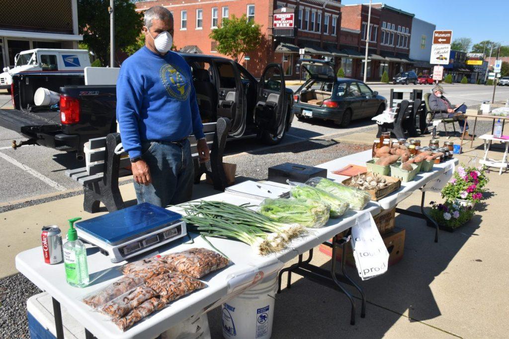 Mike Henry of Okawville stands beside his table at the Farmer's Market in Nashville Thursday morning.